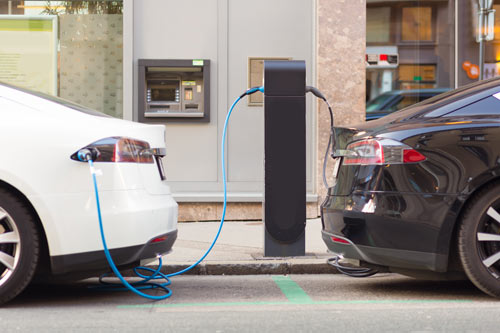 image of white and black electric vehicles charging